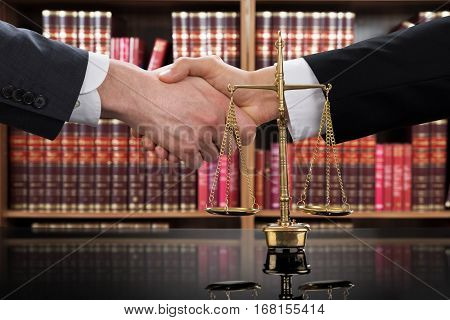 Close-up Of A Justice Scale With Judge And Client Shaking Hands In A Courtroom