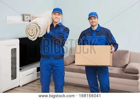 Portrait Of A Two Male Movers Carrying Rolled Carpet And Cardboard Box In House