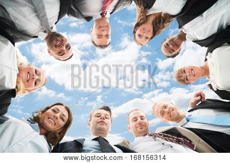 Portrait Of A Multiethnic Businesspeople Forming Huddle Against Sky