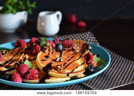 Vanilla pancakes with berries and chocolate sauce on a dark background