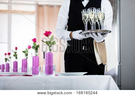 Waiter Standing With Champagne Glasses Next To Arranged Wedding Table