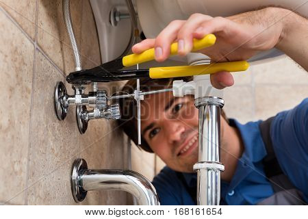Close-up Of Male Plumber Installing Kitchen Sink Using Wrench