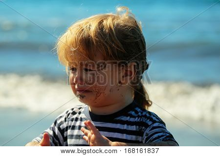 Cute unhappy baby boy with dirty face and hair blond in blue striped tshirt crying on sunny summer day on blurred blue sea background