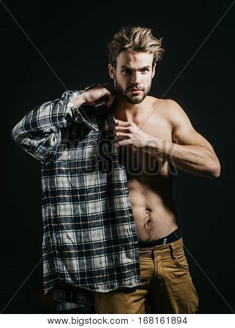 Sexy young handsome naked man with messy hair in beige pants wears plaid shirt on dark background