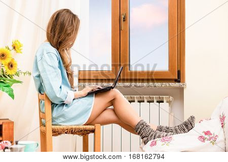 Sensual woman typing at pc laptop sitting on chair by the window at home - Fresh girl silhouette using computer on legs relaxing in cozy atmosphere near radiator inside house - Warm indoors tones