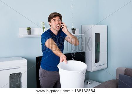 Worried Man Calling Plumber While Leakage Water Falling Into Bucket At Home