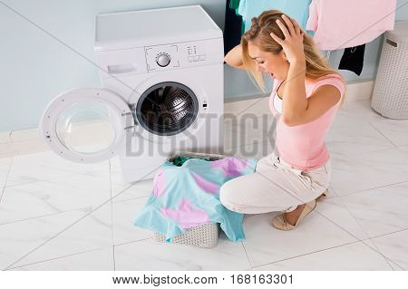 Young Shocked Woman Looking At Stained Bleached Clothes Near Washing Machine At Utility Room