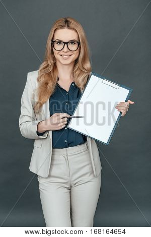 I need your signature here! Gorgeous woman in smart casual wear pointing on blank paper and looking at camera while standing against grey background