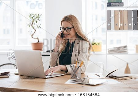 Important business talk. Confident young woman in smart casual wear talking on the mobile phone and smiling while sitting at her working place in creative office