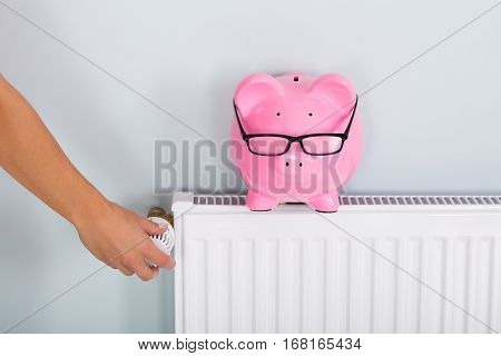 Person Hand Adjusting Thermostat To Reduce Heating To Save Money On Energy Bill