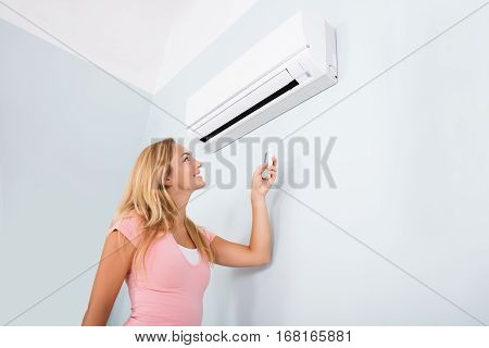 Portrait Of A Happy Woman Holding Remote Control In Front Of Air Conditioner At Home