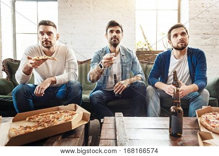 Choosing a TV channel. Nice bearded delighted man holding a remote control and choosing a channel while watching TV with his friends
