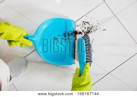 Close-up Of Person Wearing Gloves Sweeping Floor With Broom And Dustpan