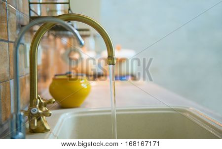 modern, trendy, bronze faucet in a new modern kitchen. From the tap is flowing tap water