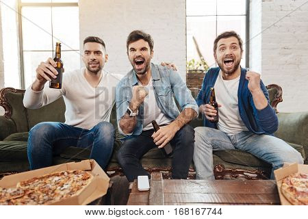 A scored goal. Good looking joyful jubilant men holding bottles of beer and laughing while cheering for their football team