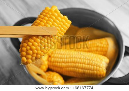 Wooden tongs with tasty boiled corncob, close up