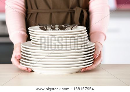 Young woman with pile of dishware on kitchen, closeup