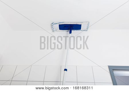 Low Angle View Of Mop Wiping On The Ceiling Of The Bathroom