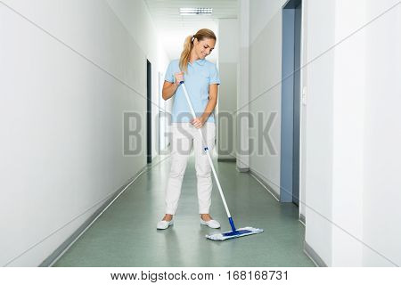 Happy Female Janitor Cleaning The Floor With Mop On The Corridor Of The Building