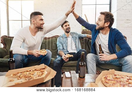 Best friends. Handsome nice delighted men looking at each other and giving high five while enjoying their home party