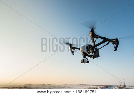 quadrocopter drone with remote control. Dark silhouette against colorfull sunset. Soft focus. Toned image