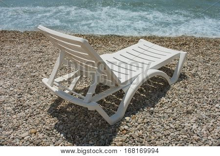 White Chaise Lounge On The Beach
