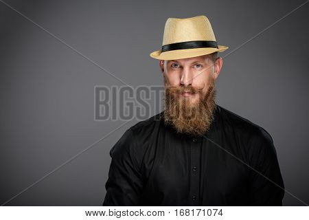 Closeup of hipster man with beard and mustashes wearing black shirt and straw fedora hat, over grey background