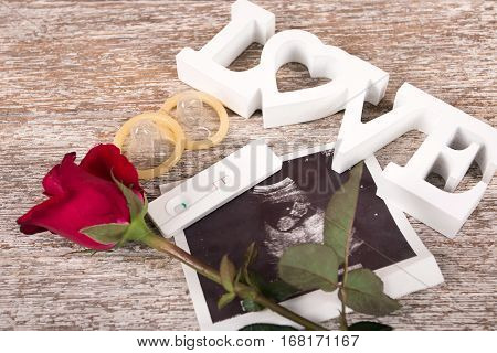 concept valentine day red rose and text love on brown wooden background vintage tone