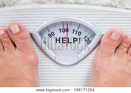Close-up Of Overweight Person Feet On Weight Scale Indicating Help
