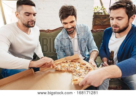 We love food. Attractive young brutal man sitting together and taking slices of pizza while intending to eat it