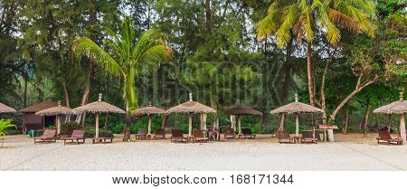 Wooden Chairs And Umbrellas On White Beach