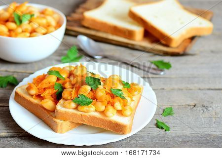 Baked beans on bread. Beans baked with vegetables in a bowl, bread slices on a chopping board, spoon, fresh parsley leaves on a wooden table. Vegan and vegetarian protein source. Vintage style