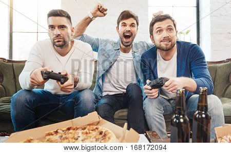 Interesting entertainment. Nice good looking young men holding game consoles and playing video games while having fun together