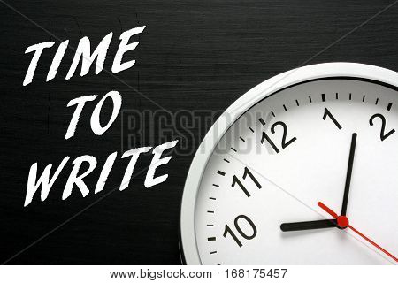 The words Time To Write in white text on a blackboard next to a clock as a reminder to aspiring authors to get down to work