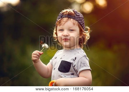 little boy in the garden with a dandelion in his hand on which the butterfly sits