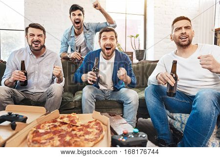 Absolute happiness. Happy jubilant handsome men holding bottles of beer and expressing their emotions while watching football on TV