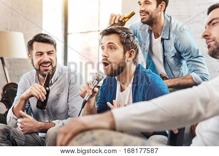 Sinking karaoke. Nice handsome delighted man holding a microphone and singing a song while singing karaoke