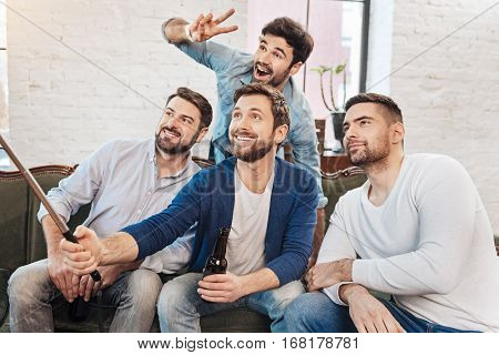 Now smile. Joyful positive bearded man holding a selfie stick and taking a photo while posing on a camera with his friends
