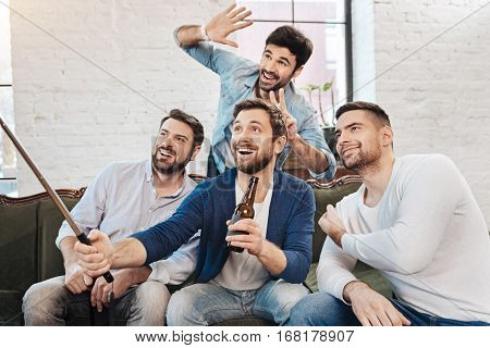Selfie time. Handsome cheerful male friends smiling and looking into the camera while posing for a photo