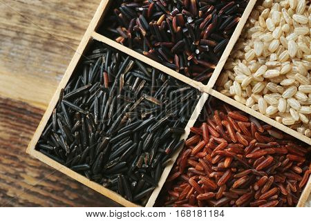 Different types of rice in wooden compartment box, top view