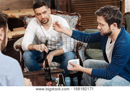 Do you see this card. Pleasant positive brutal man holding a card and showing it to his friends while shuffling the pack of playing cards