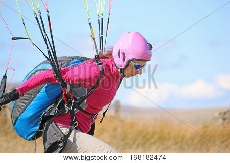 Paraglider launching herself from a hill top