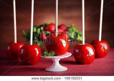 Candy apples on red wooden table