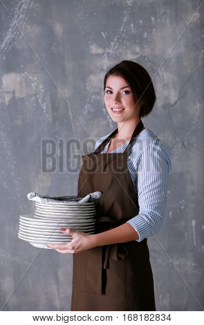 Young woman with pile of dishware on grunge background