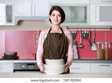 Young woman with pile of dishware on kitchen at home
