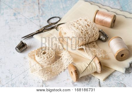 Sewing supplies and accessories for needlework.  Fabric, openwork lace, spools of thread, scissors and thimbles on an old wooden table.