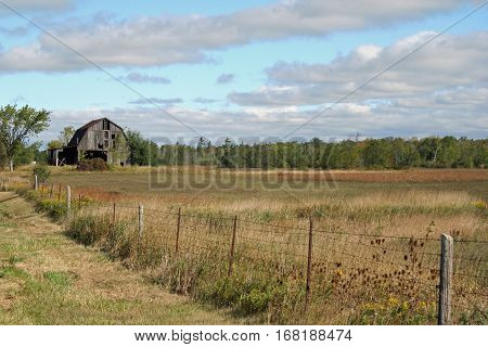 Old, forgotten barn sitting in a farm field