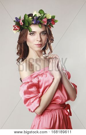 Gentle romantic appearance of the girl with a wreath of roses on her head and a pink dress. Joyful Jolly spring woman. Summer lady in long pink dress