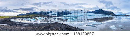 Panorama image of Iceland's Secret Lagoon.  The site is full of glaciers and icebergs surrounded by mountains and a rocky, rugged shoreline. Shot with seven images.