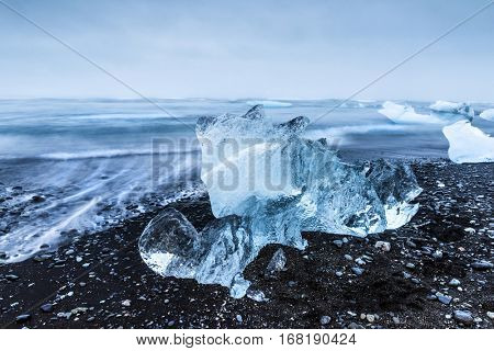An iceberg along the shore of Jokulsarlon glacial lagoon rests motionless as it is framed by cold ocean water.